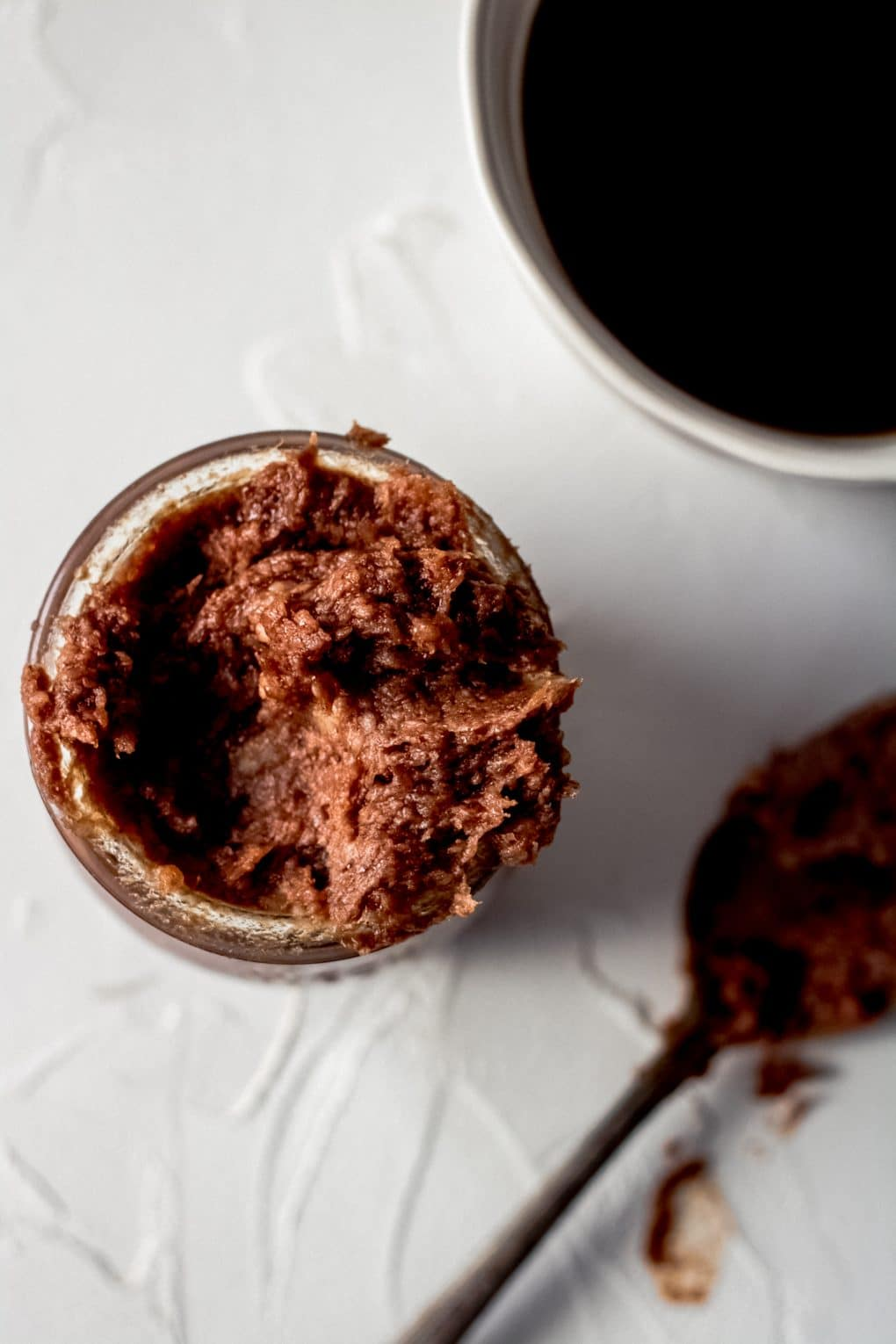 an overhead shot of mocha coconut oil coffee creamer in a  small glass jar. There is a cup of coffee and spoon nearby