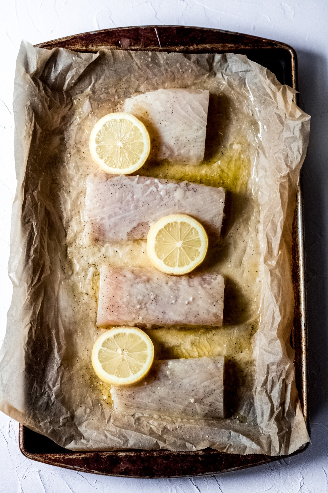 a baking sheet lined with parchment paper with four raw Mahi Mahi fillets and lemon slices