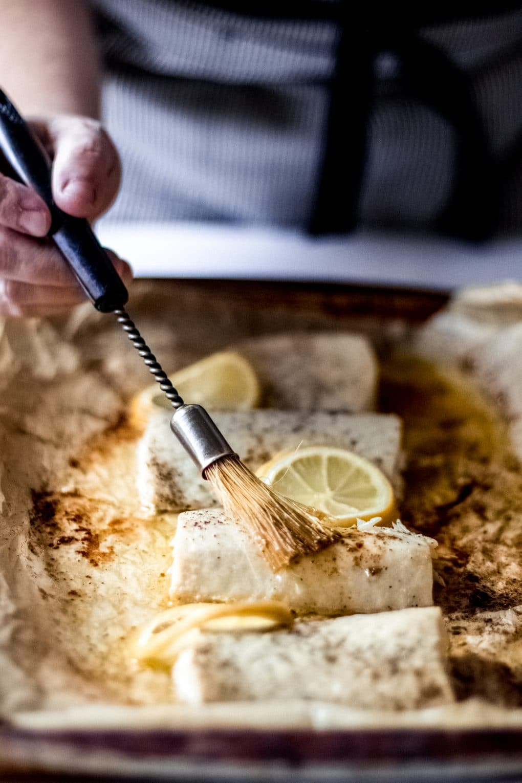 a woman using a basting brush to baste Mahi Mahi fillets with melted lemon butter