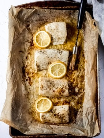 a sheet pan covered in parchment paper with four Mahi Mahi fillets, melted butter, slices of lemon, and a basting brush