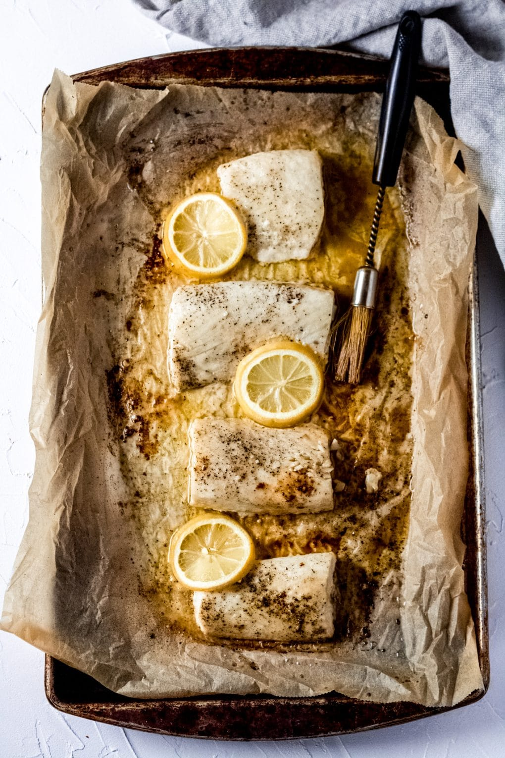 four mahi mahi fillets on brown parchment paper on a baking sheet. There are lemon slices on the fillets and a basting brush laying beside them.