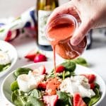 someone pouring strawberry basil homemade salad dressing over a strawberry basil burrata salad