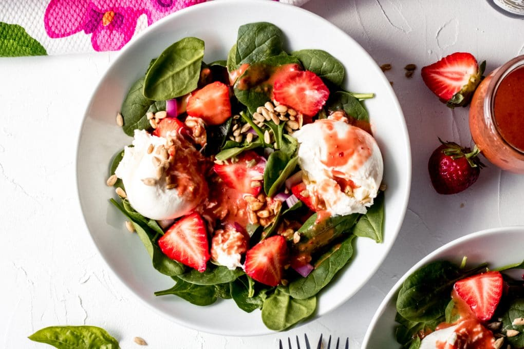 a white bowl featuring a strawberry basil burrata salad. There are fresh strawberries laying nearby and a jar of homemade strawberry basil salad dressing