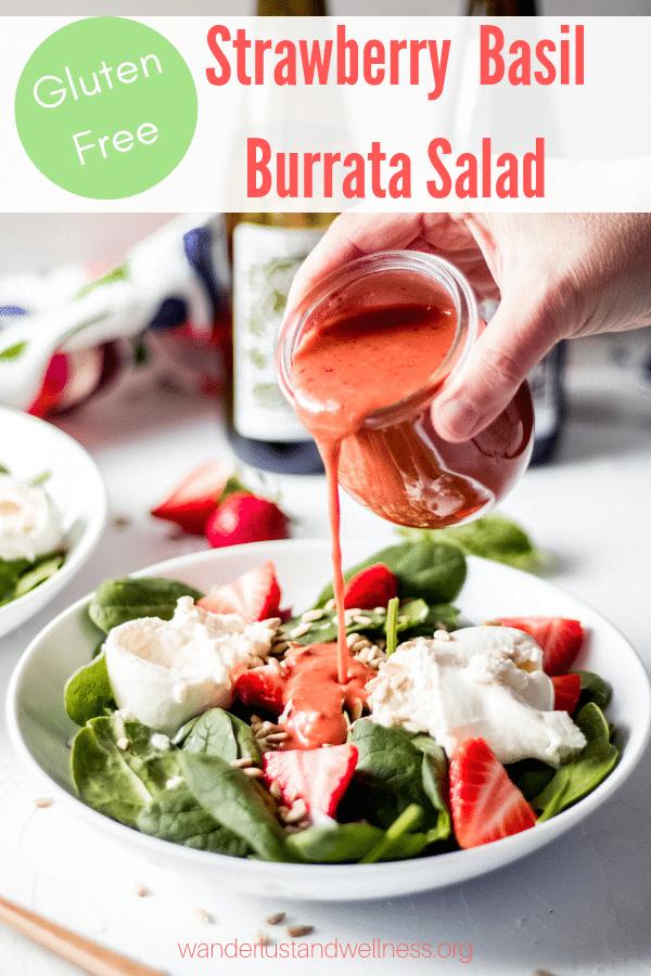 a woman pouring homemade strawberry basil dressing over a strawberry basil burrata salad