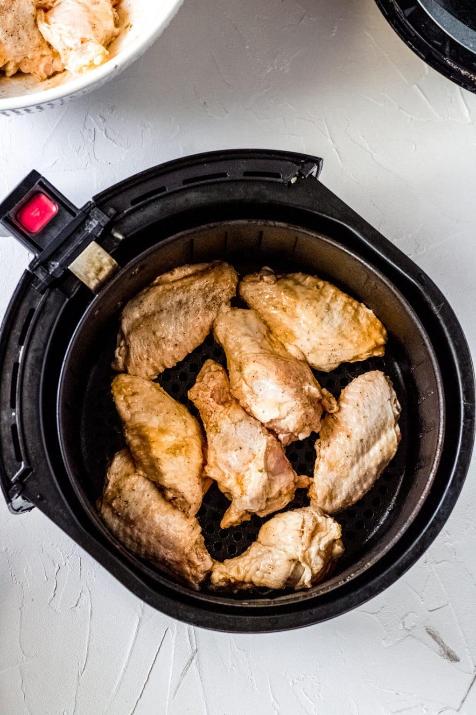 uncooked chicken wings in air fryer basket