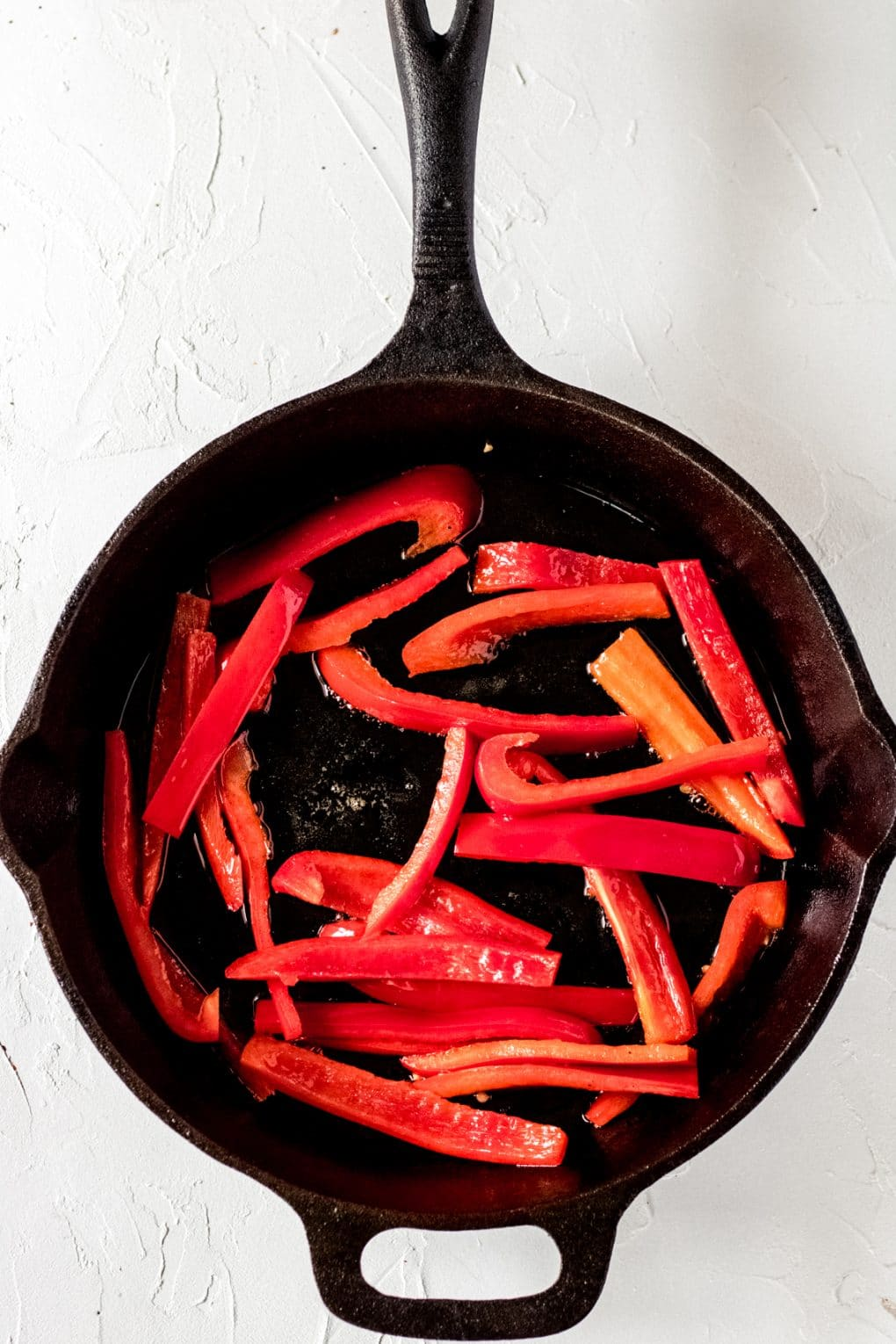 a cast iron skillet with sliced red pepper cooking