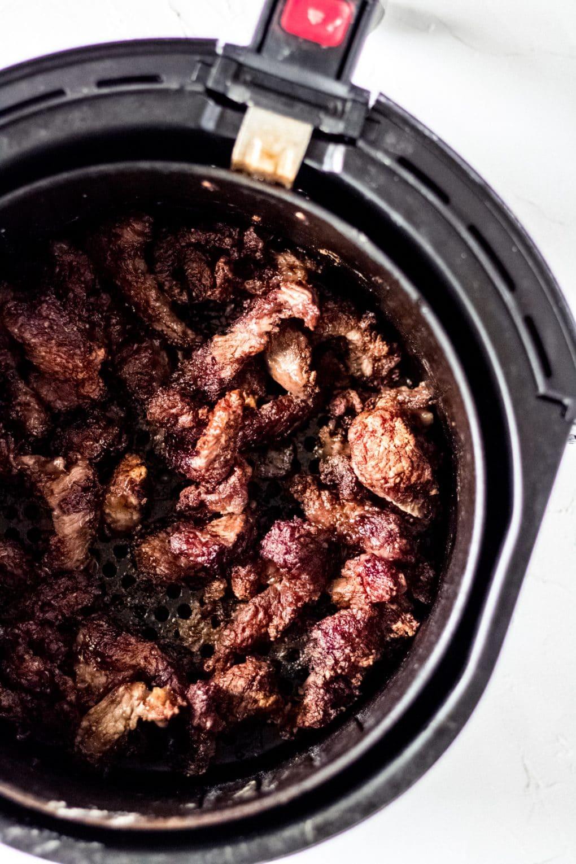 cooked sirloin steak in an air fryer basket