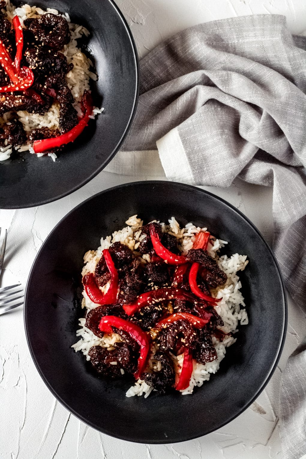 two black bowls with white rice and air fryer sticky asian beef served on top