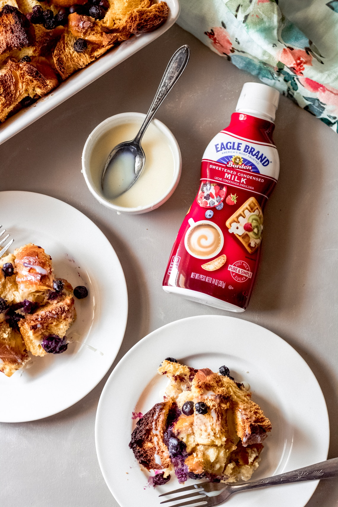 two servings of blueberry french toast bake on white plates and a bottle of Eagle Brand® sweetened condensed milk