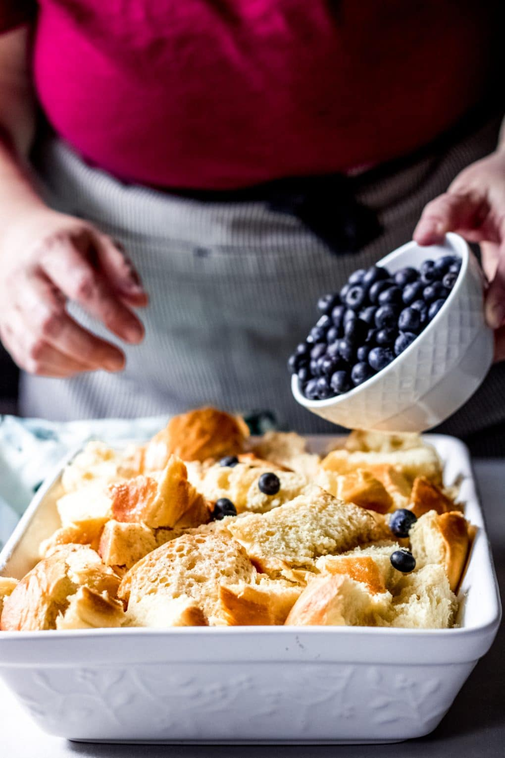 a woman adding fresh blueberries on top of the french toast bake