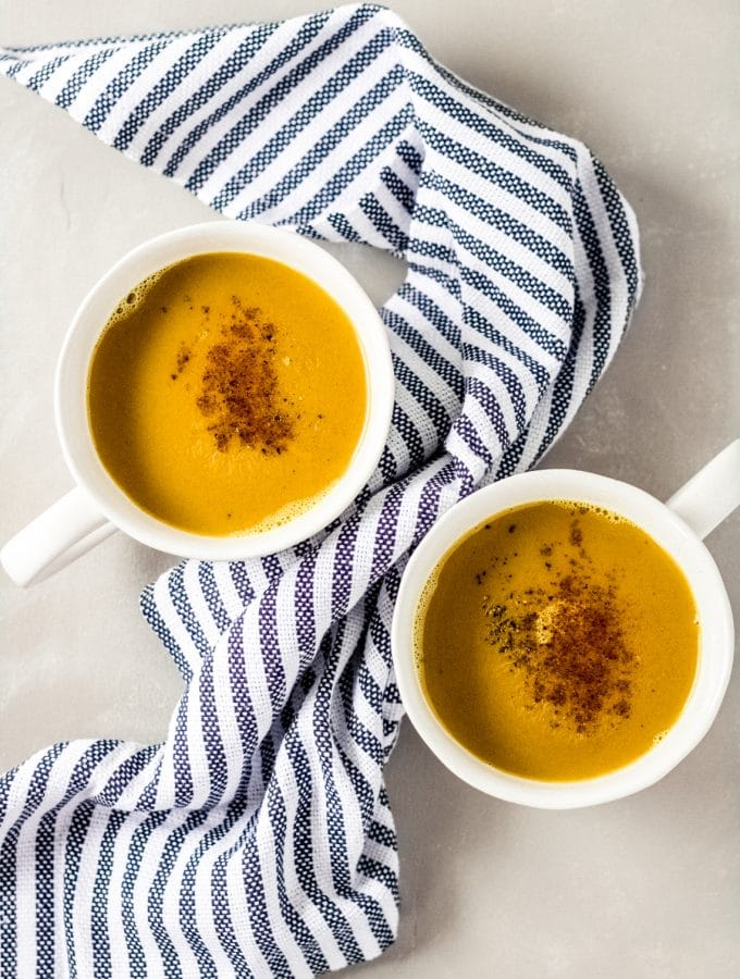 two mugs of bone broth turmeric latte - there is a navy striped towel draped between the mugs
