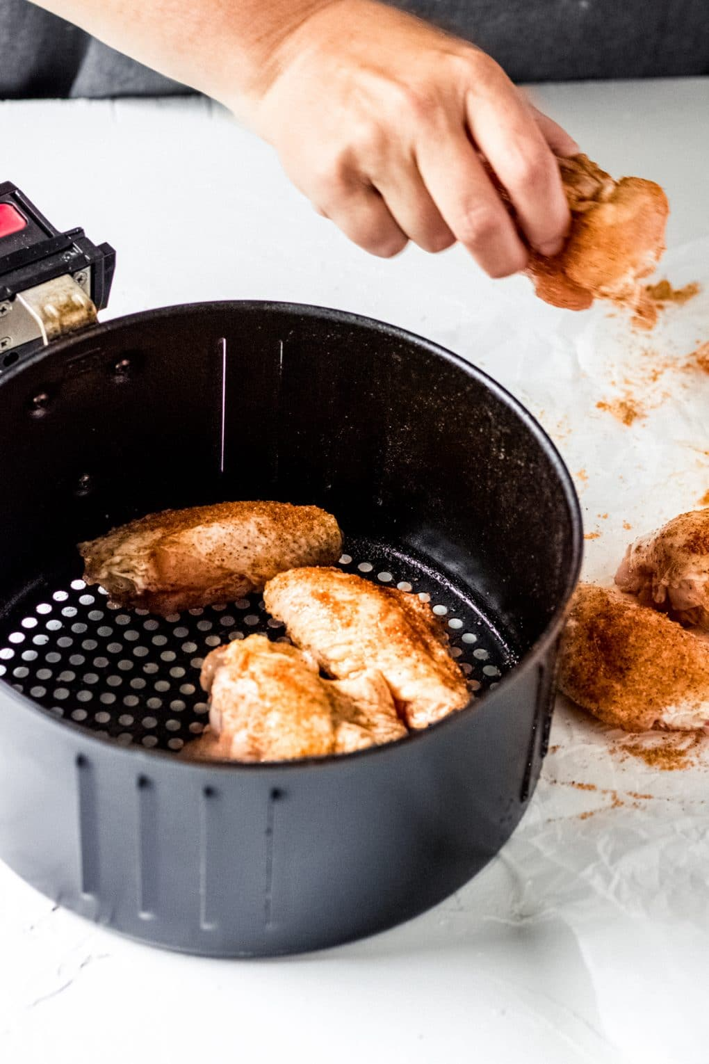 raw cajun chicken wings being placed into an air fryer basket