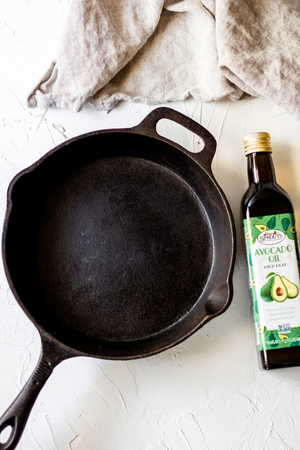 a cast iron skillet and a bottle of avocado oil
