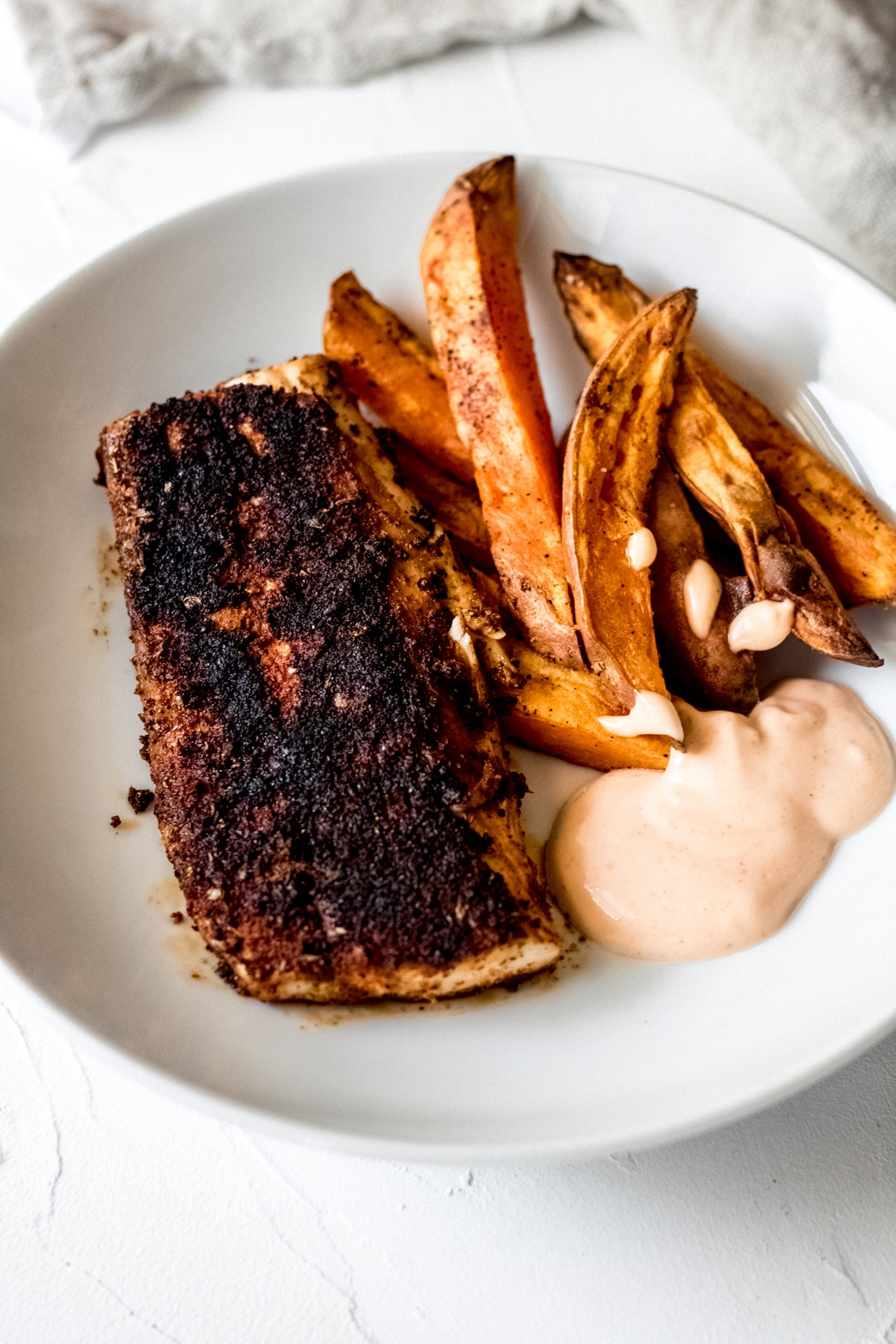 one mahi mahi fillet, sweet potato fries, and dipping sauce in a white bowl
