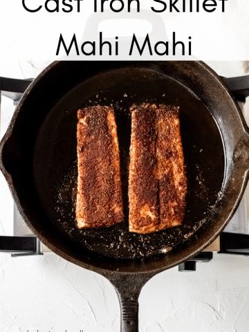 two mahi mahi fillets in a cast iron skillet