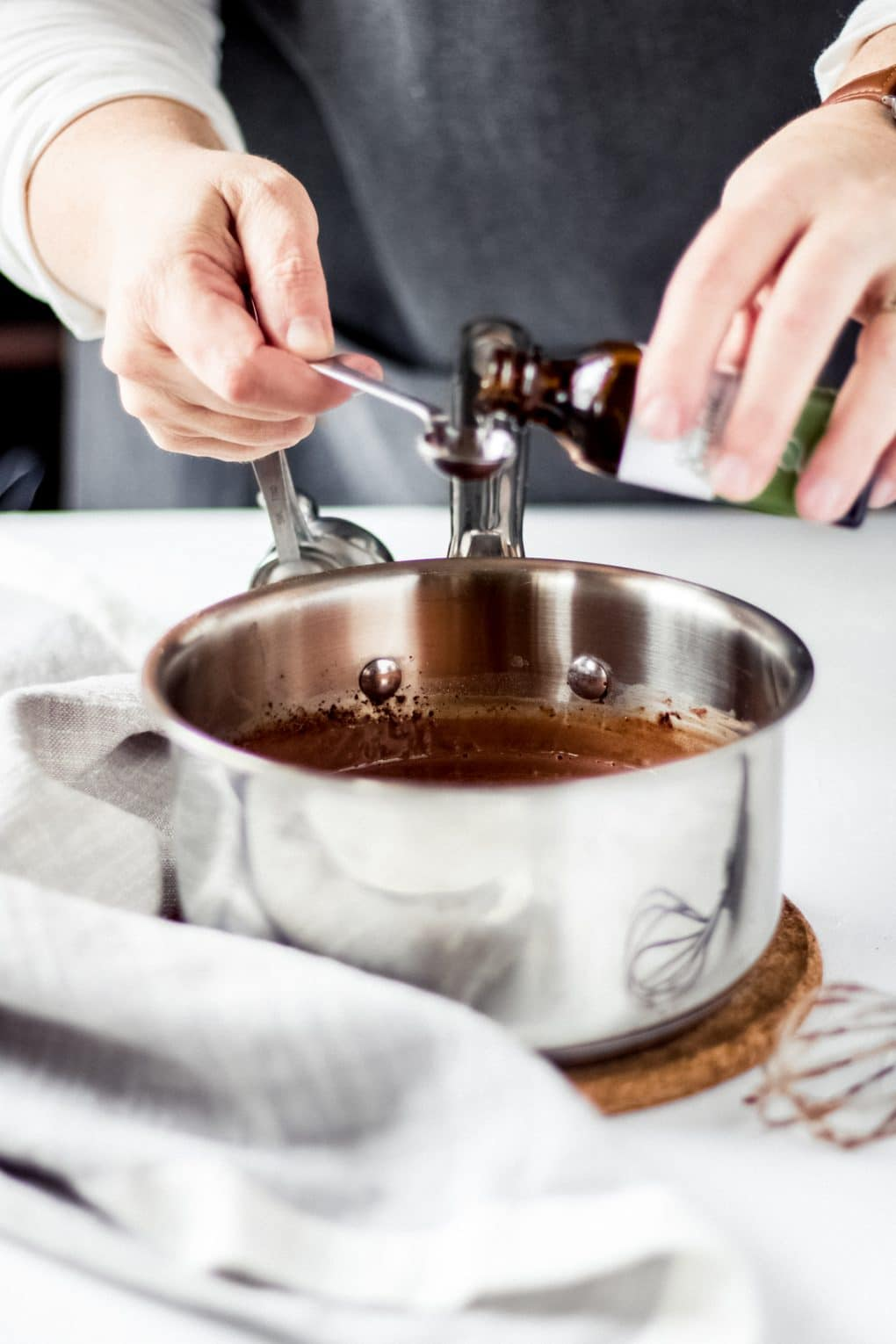 a woman adding peppermint extract to a saucepan