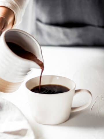 a woman pouring dairy free sugar free mint mocha coffee creamer into a glass of coffee