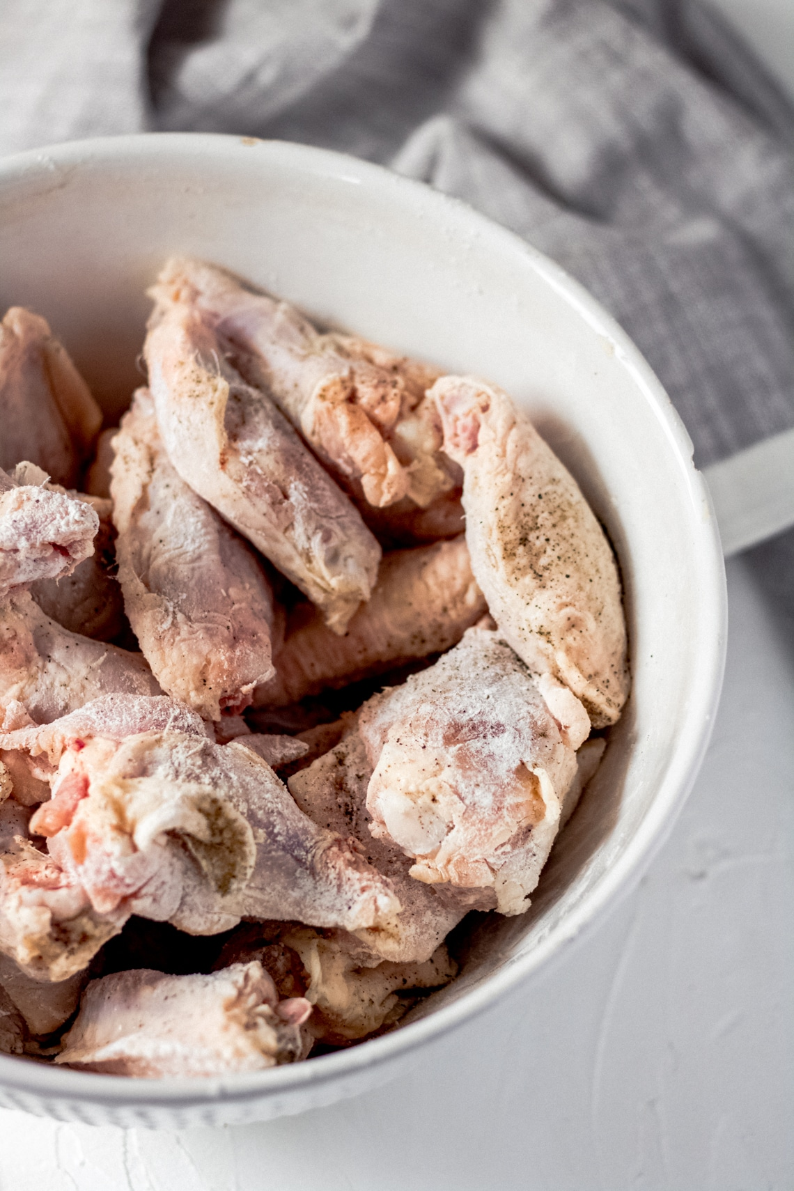a bowl of raw chicken wings