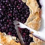 a baked gluten-free blueberry galette with one slice cut out of it