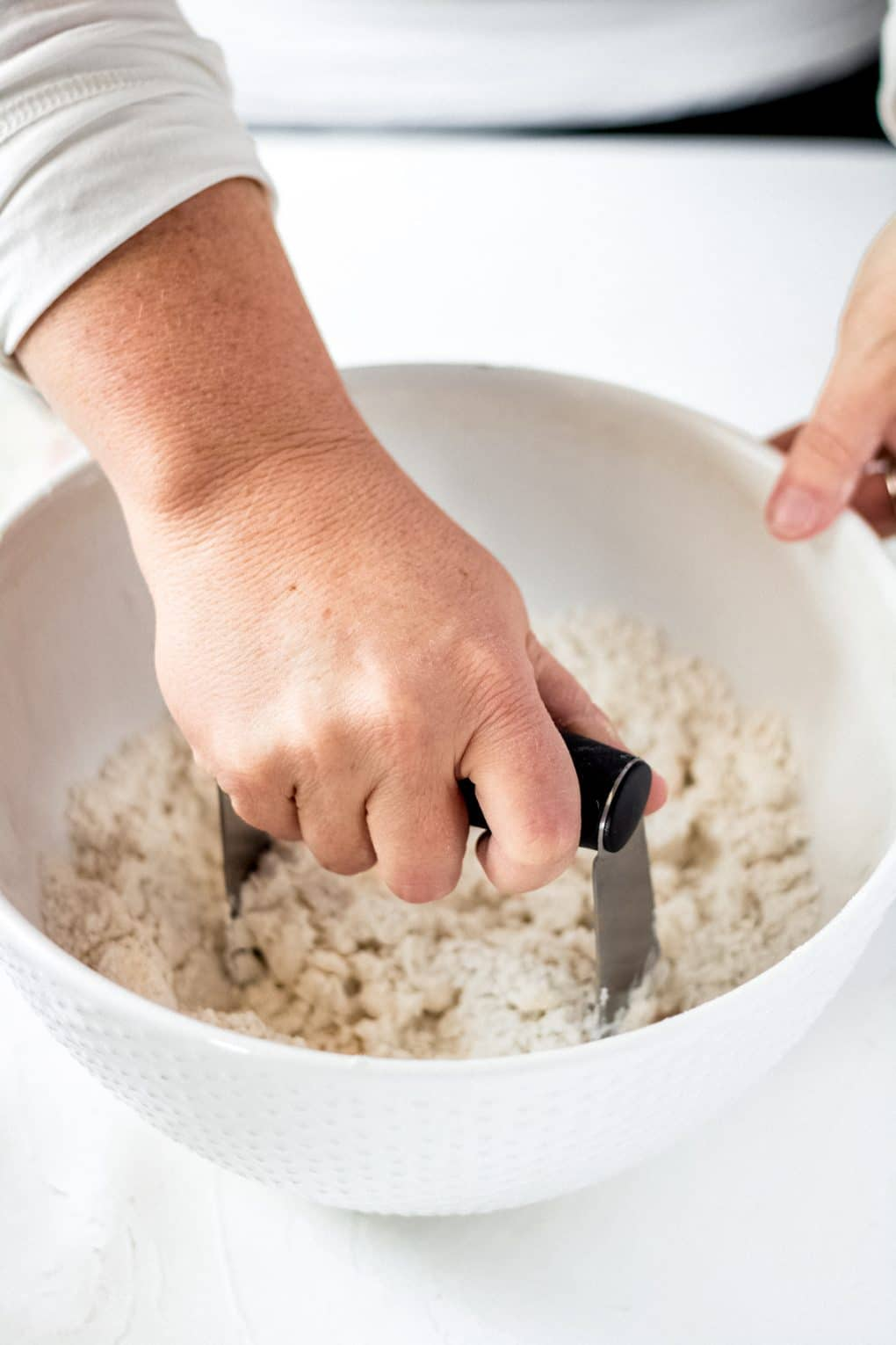 a woman cutting in butter with a pastry blender