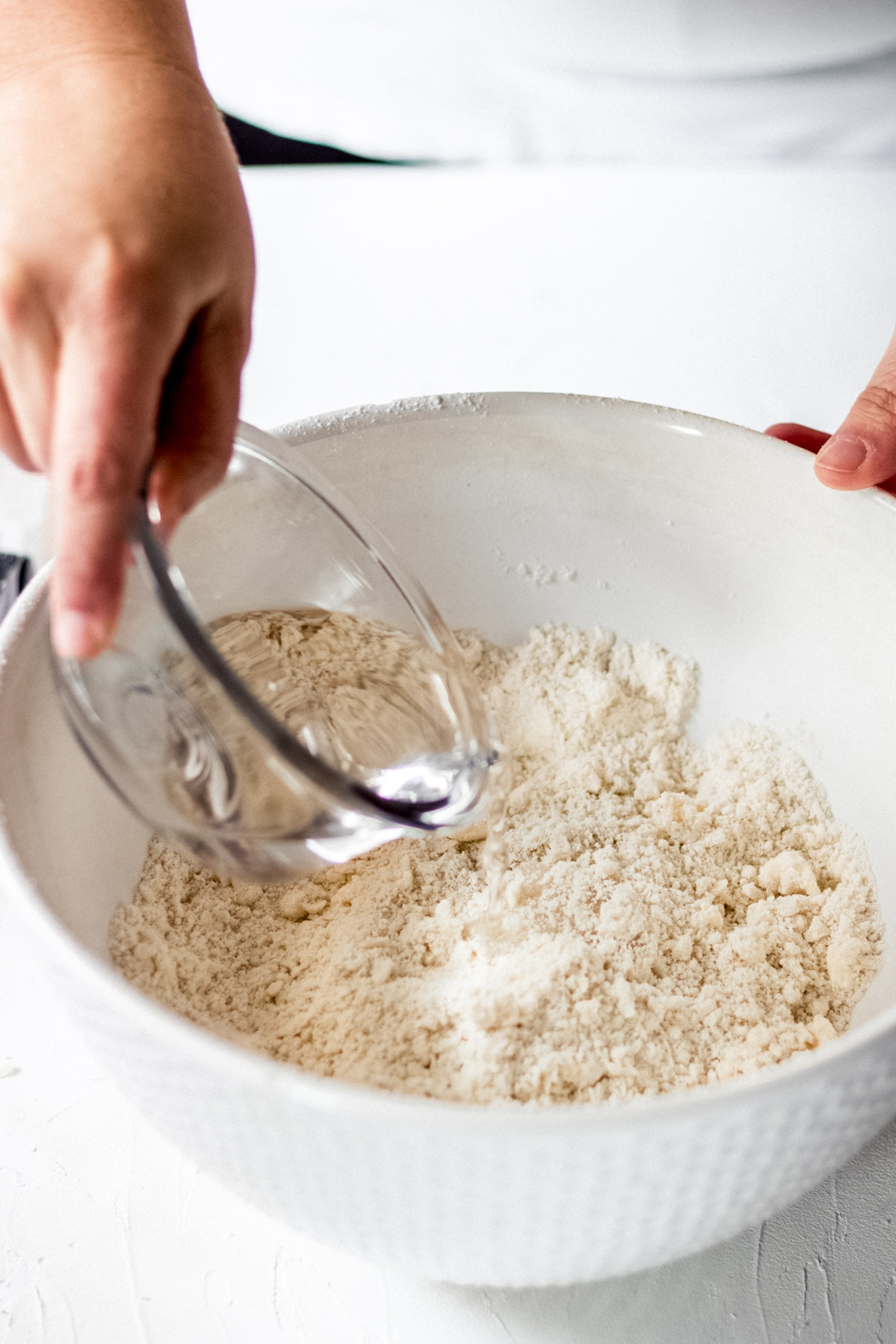 a woman pouring water onto the flour mixture