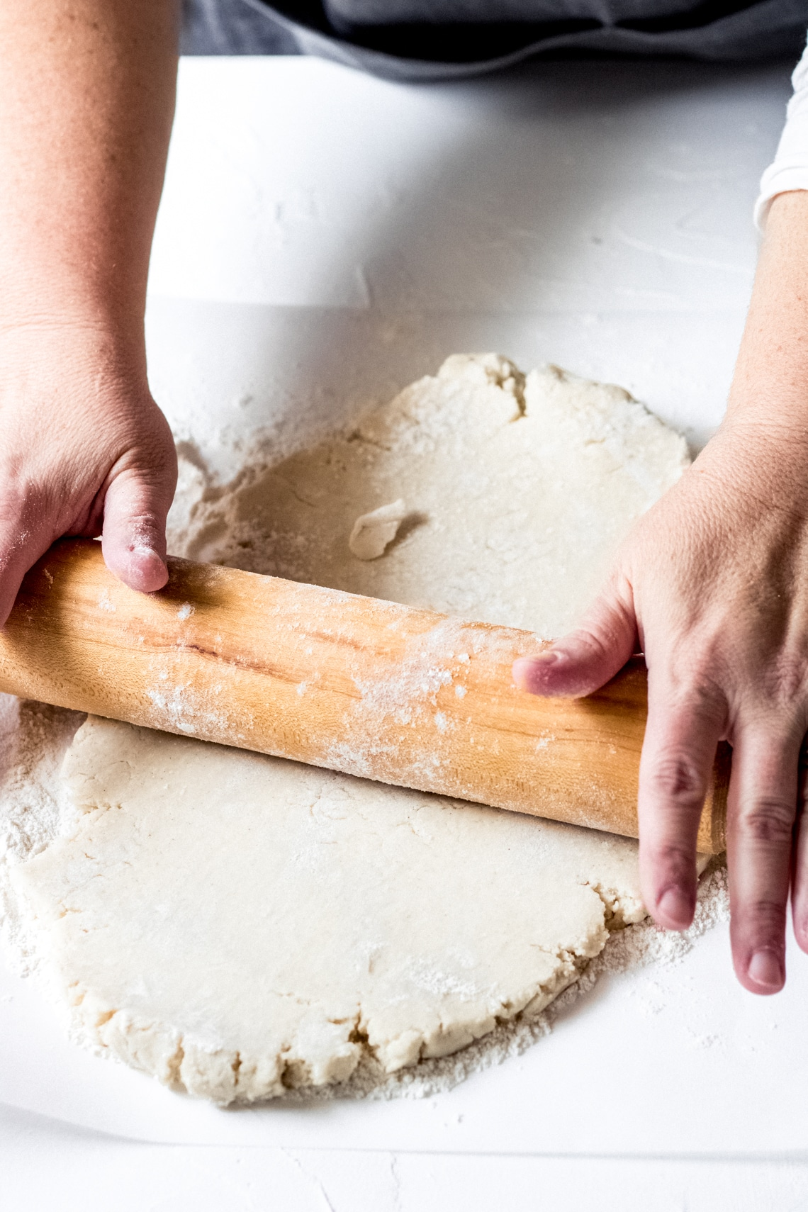 a woman rolling out gluten-free galette dough