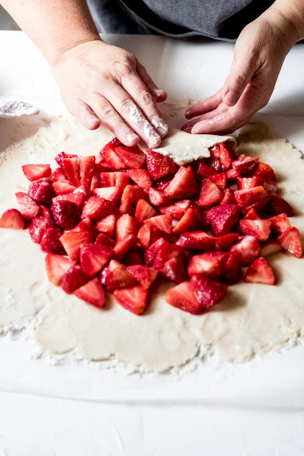 a woman folding up the sides of a gluten free strawberry galette