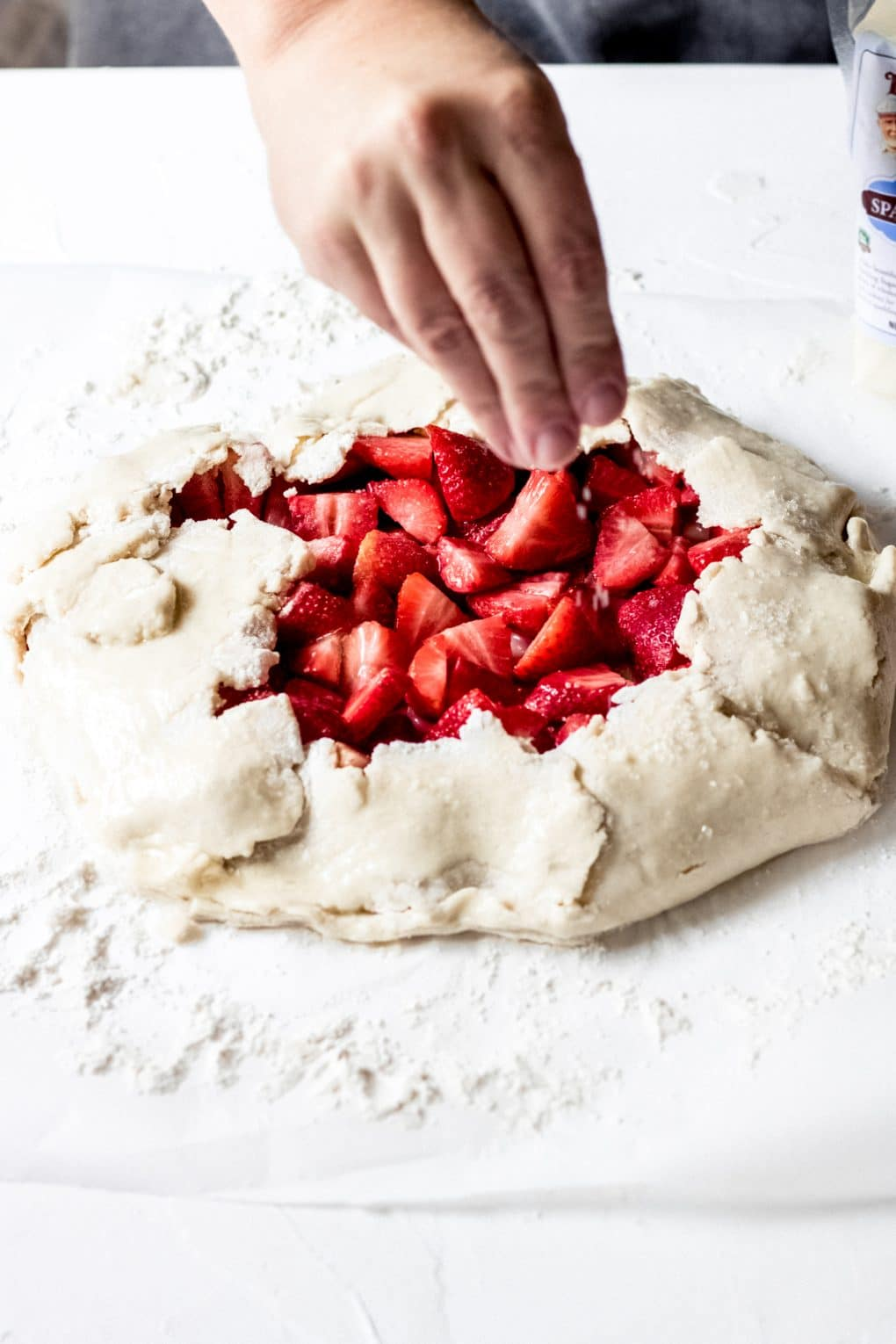 a woman sprinkling sugar over the top a strawberry galette