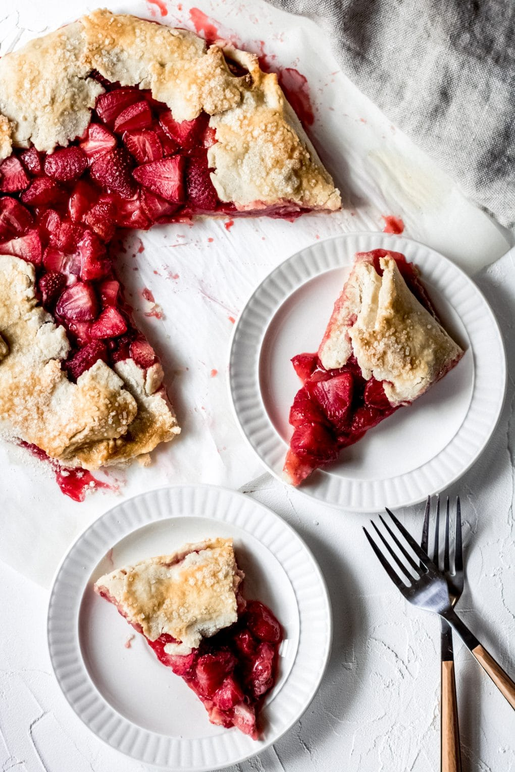 two slices of gluten-free strawberry galette on white plates