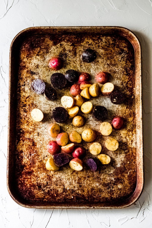 a sheet pan with sliced tiny rainbow potatoes