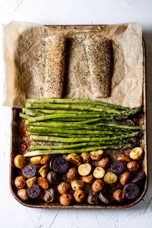 a sheet pan with tiny rainbow potatoes, uncooked asparagus and uncooked Mahi Mahi fillets