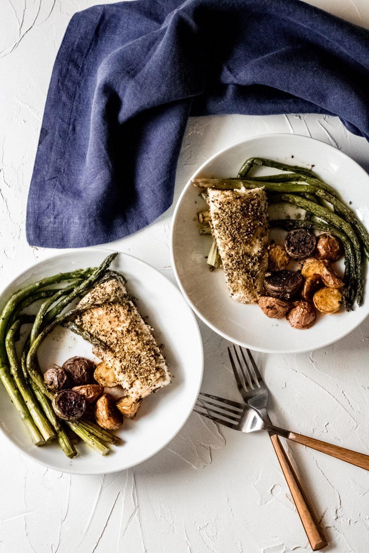two white bowls with healthy mahi mahi recipe - seasoned mahi mahi fillet, roasted tiny rainbow potatoes, and cooked asparagus