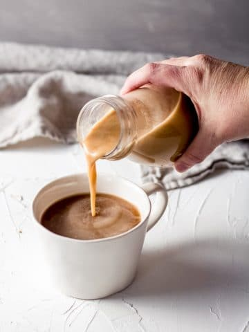 a woman pouring homemade dairy free salted caramel coffee creamer into a cup of coffee