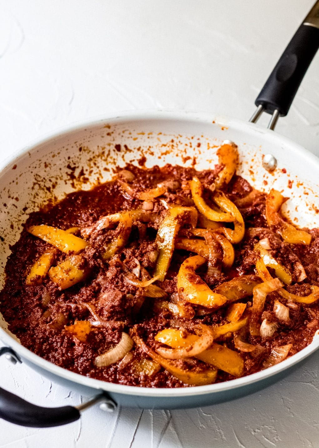 a pan of beef chorizo, peppers, and onions