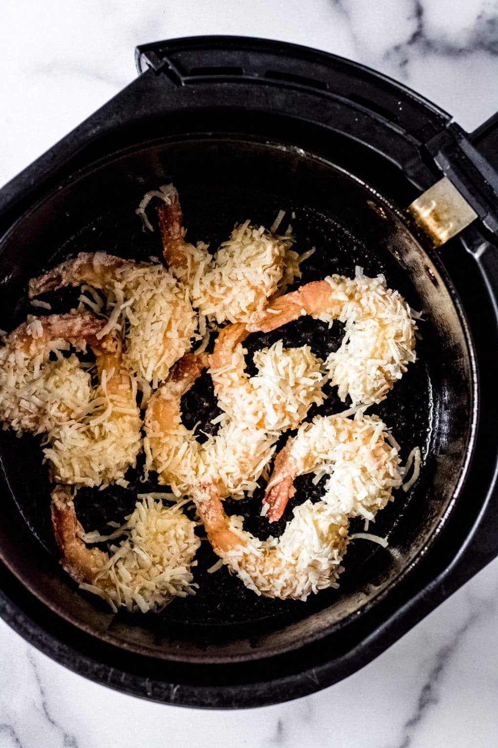 uncooked gluten-free coconut shrimp in an air fryer basket