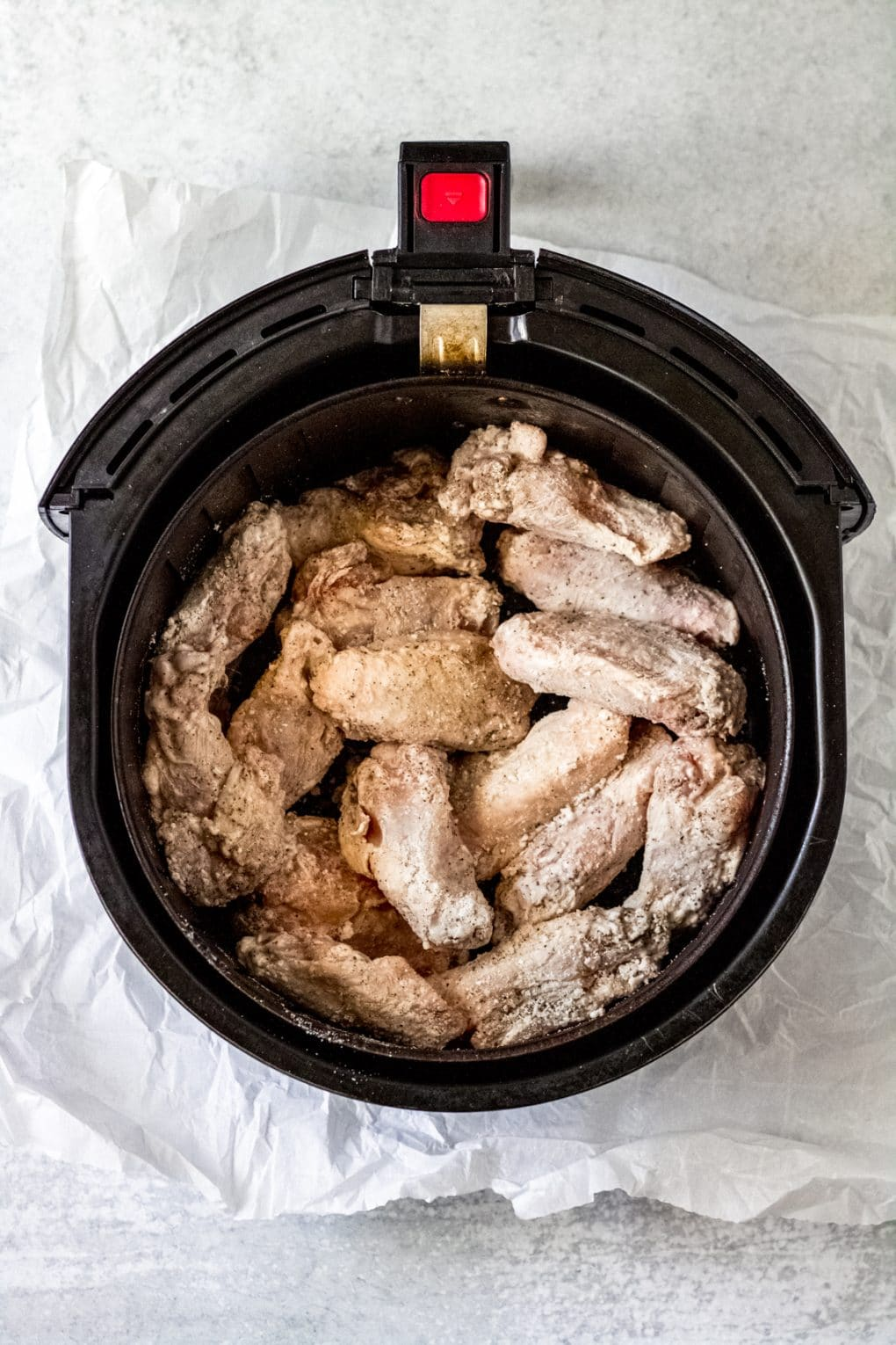 chicken wings cooking in an air fryer basket