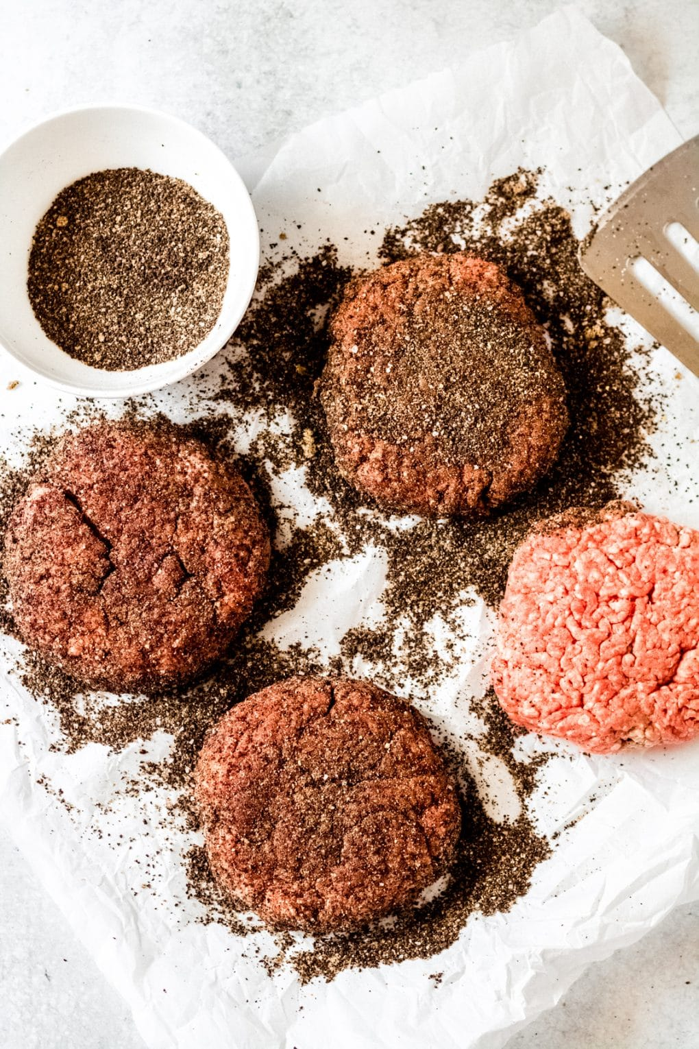 four uncooked coffee rubbed burger patties