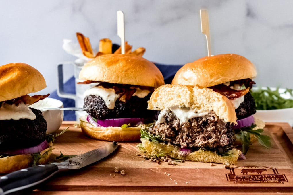 four coffee rubbed burgers on a wooden cutting board