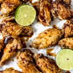 honey lime chicken wings with two lime wedges