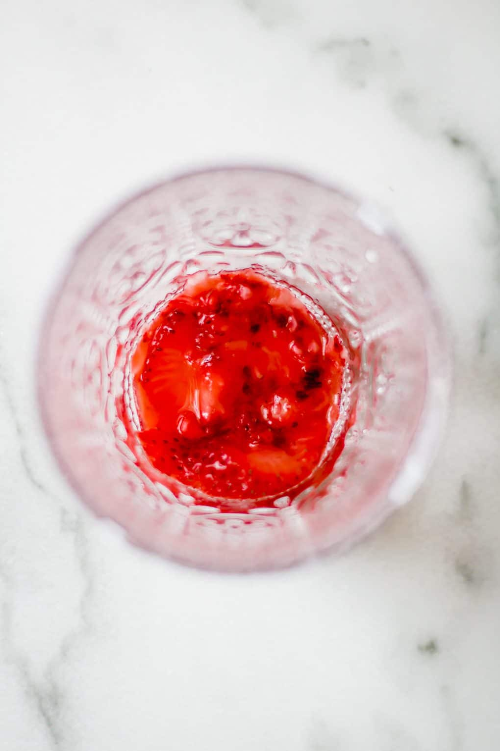 a muddled strawberry in the bottom of a glass
