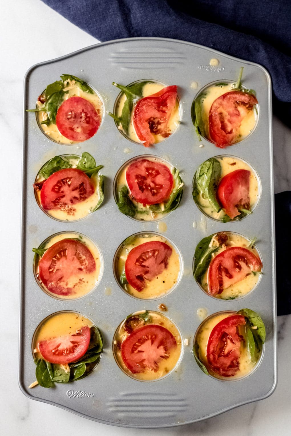 BLT egg bites uncooked in a muffin pan