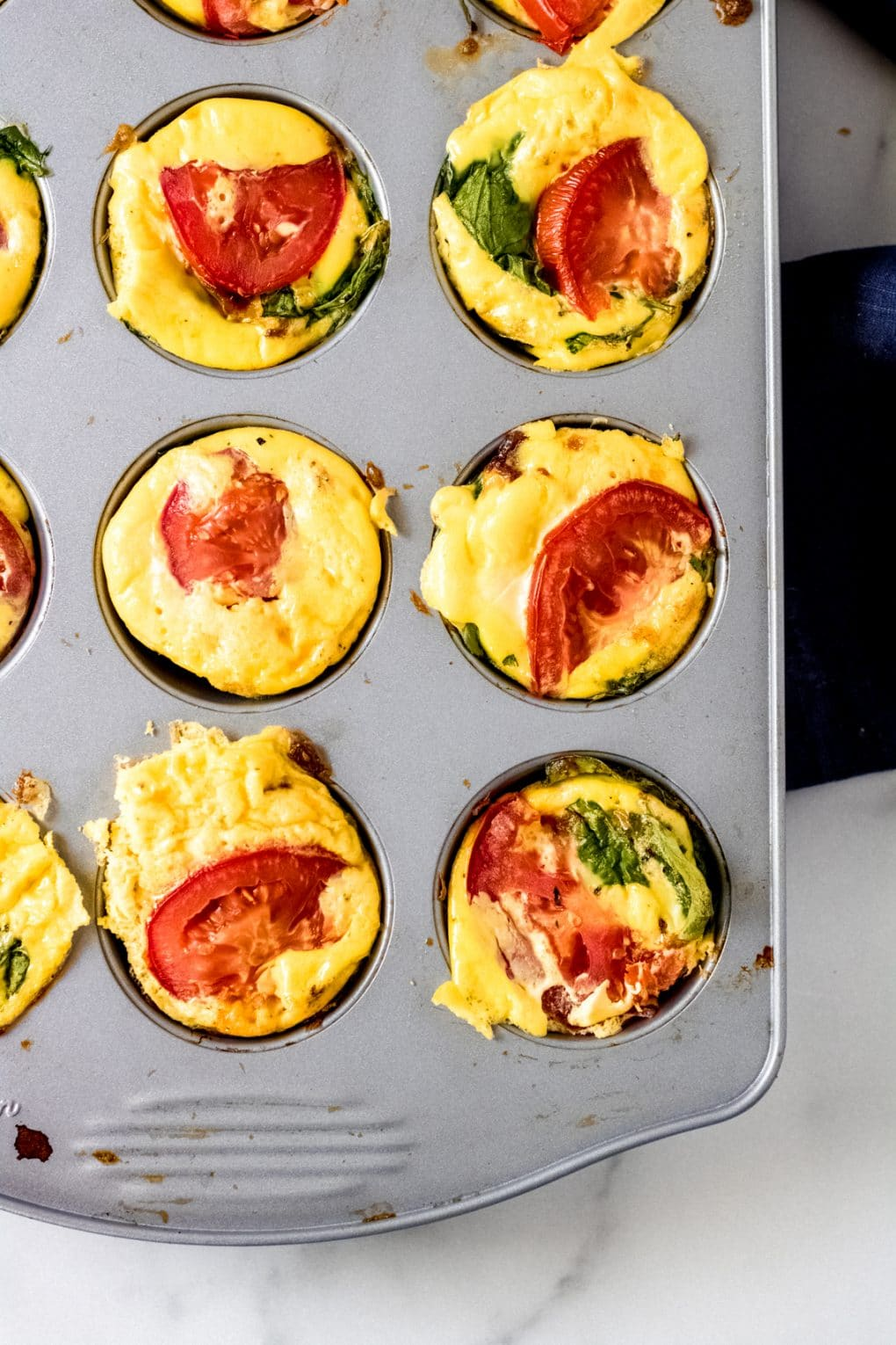 a muffin tin with gluten-free BLT breakfast egg bites baked