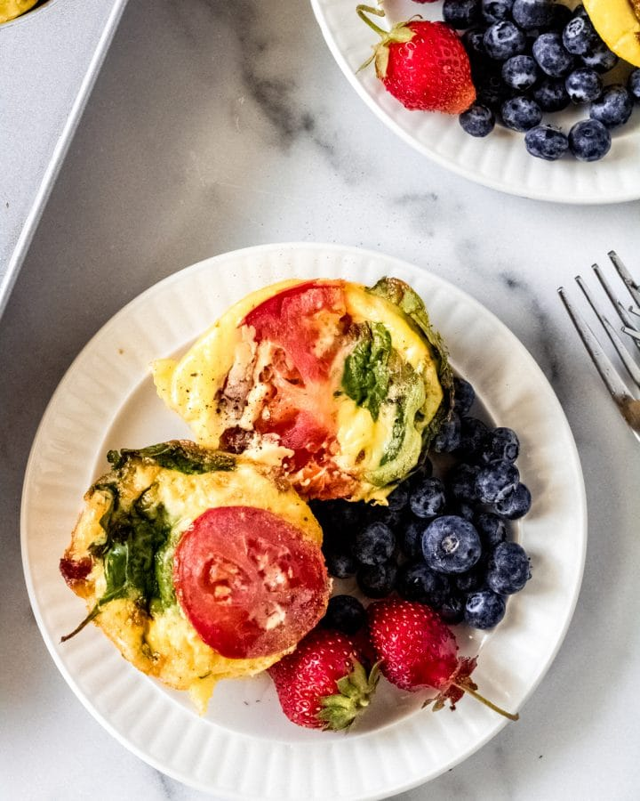 BLT breakfast egg bites on a plate with fresh strawberries and blueberries
