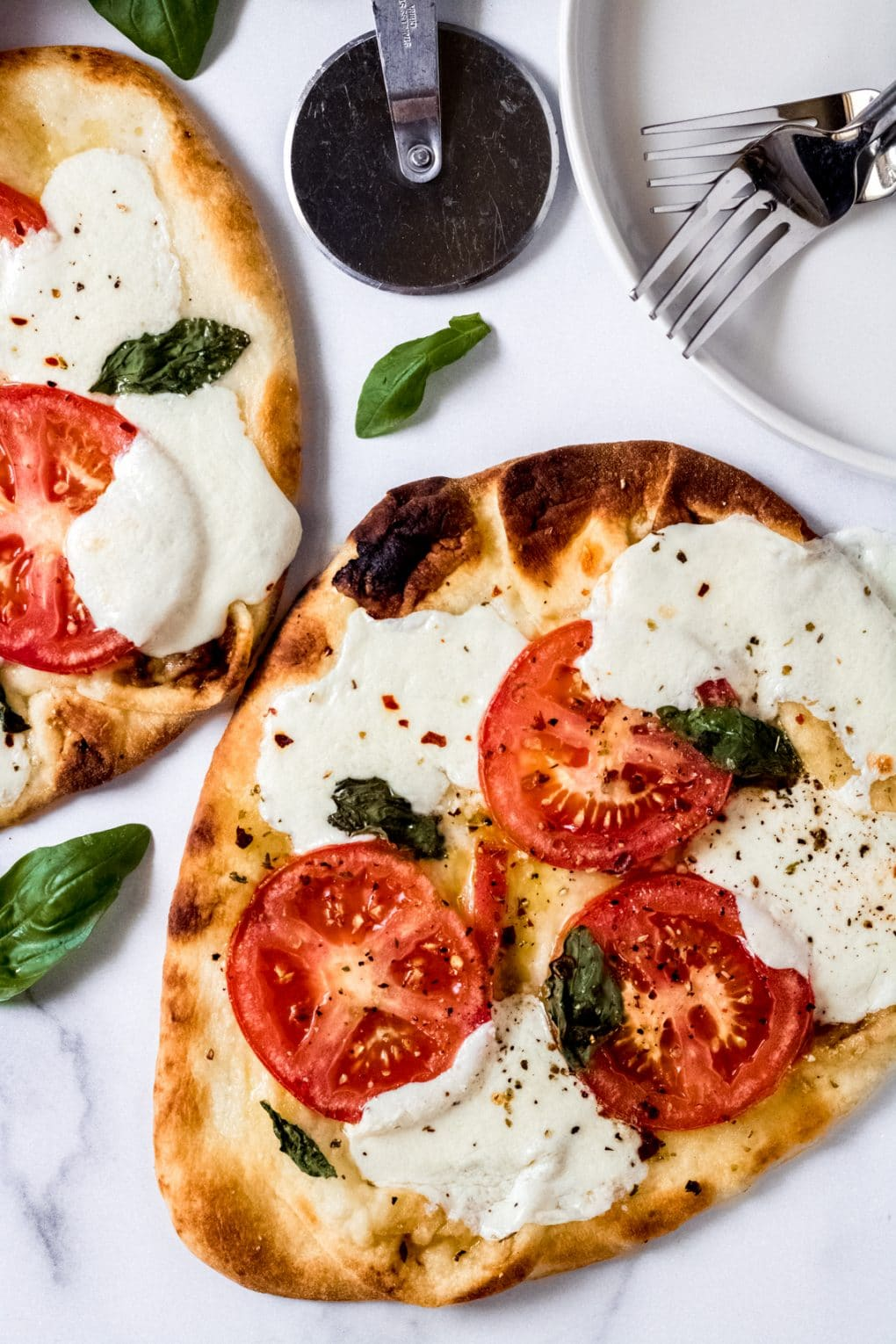 two tomato basil mozzarella flatbread pizzas
