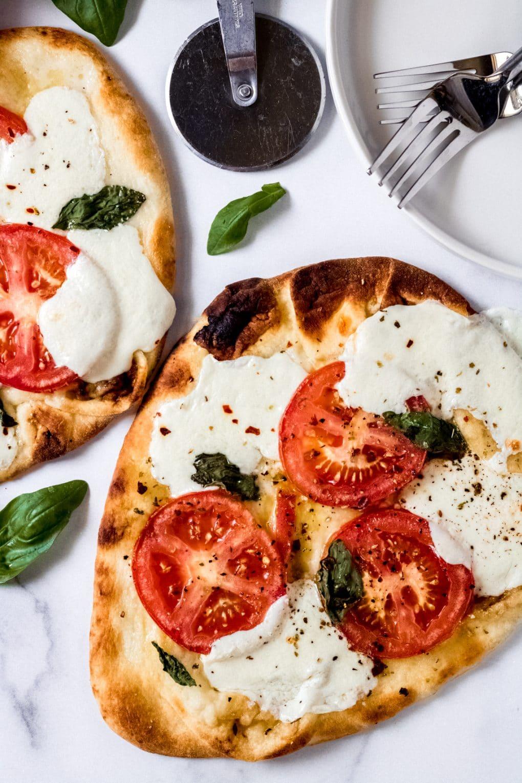 two tomato basil mozzarella flatbread pizzas