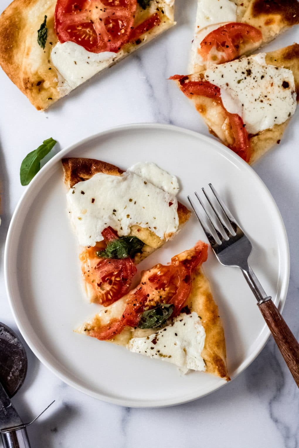 two slices of tomato basil mozzarella flatbread pizza on a white plate with a fork