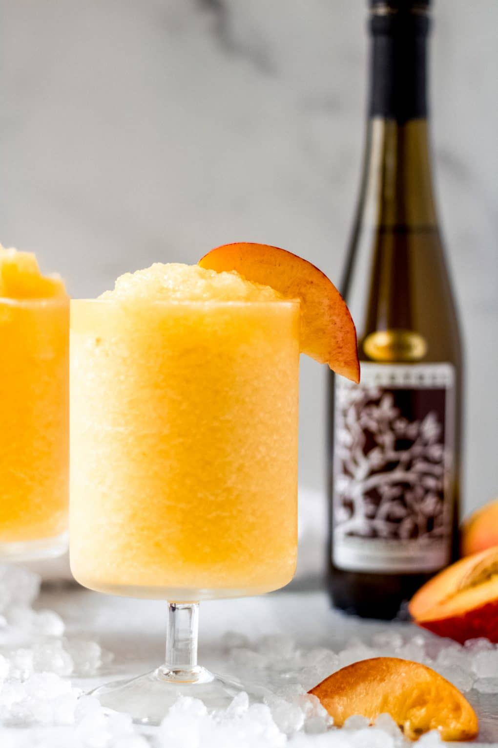 two glasses of frozen peach Bellini and a bottle of white peach balsamic vinegar