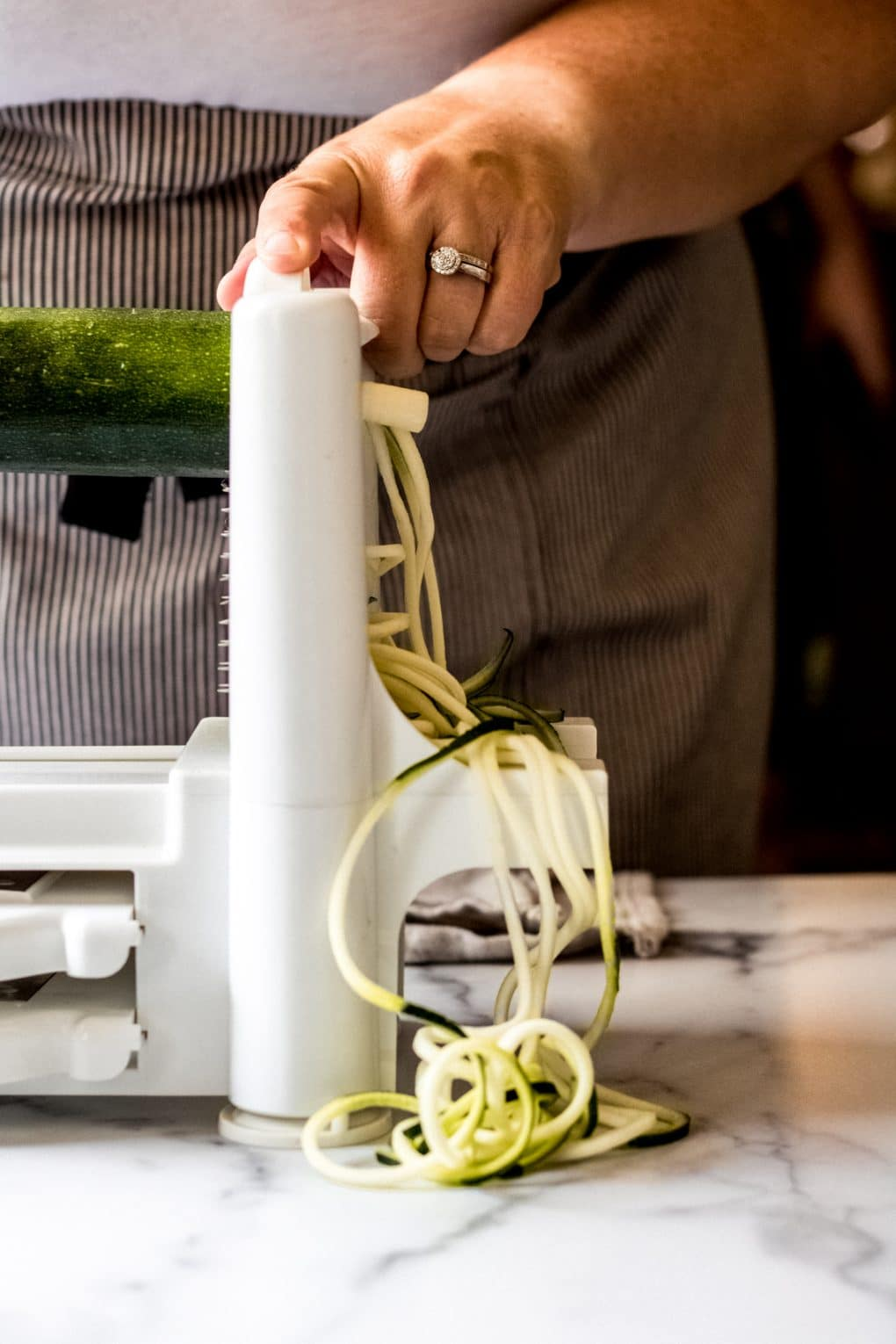a woman using a spiralizer to make zucchini noodles