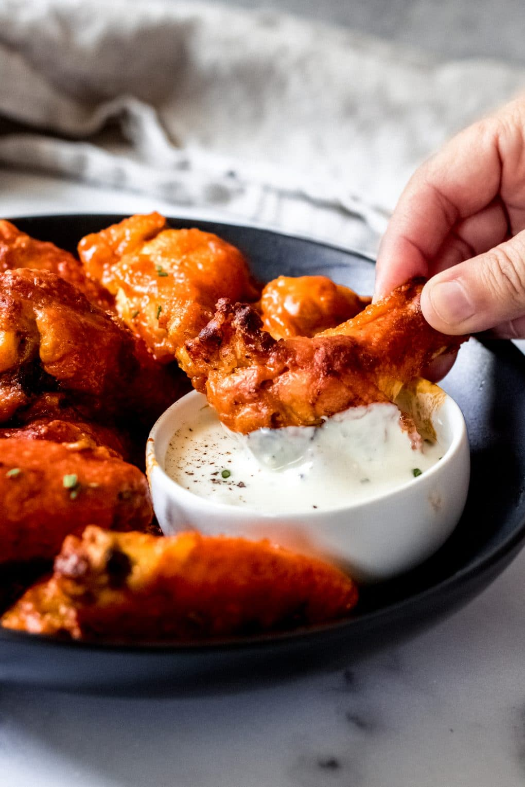 someone dipping a wing into blue cheese dressing