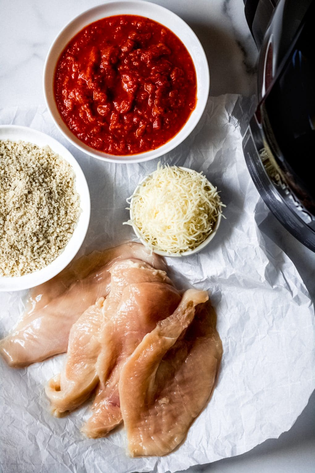 ingredients needed to make air fryer gluten-free chicken parmesan laid out on a table on parchment paper